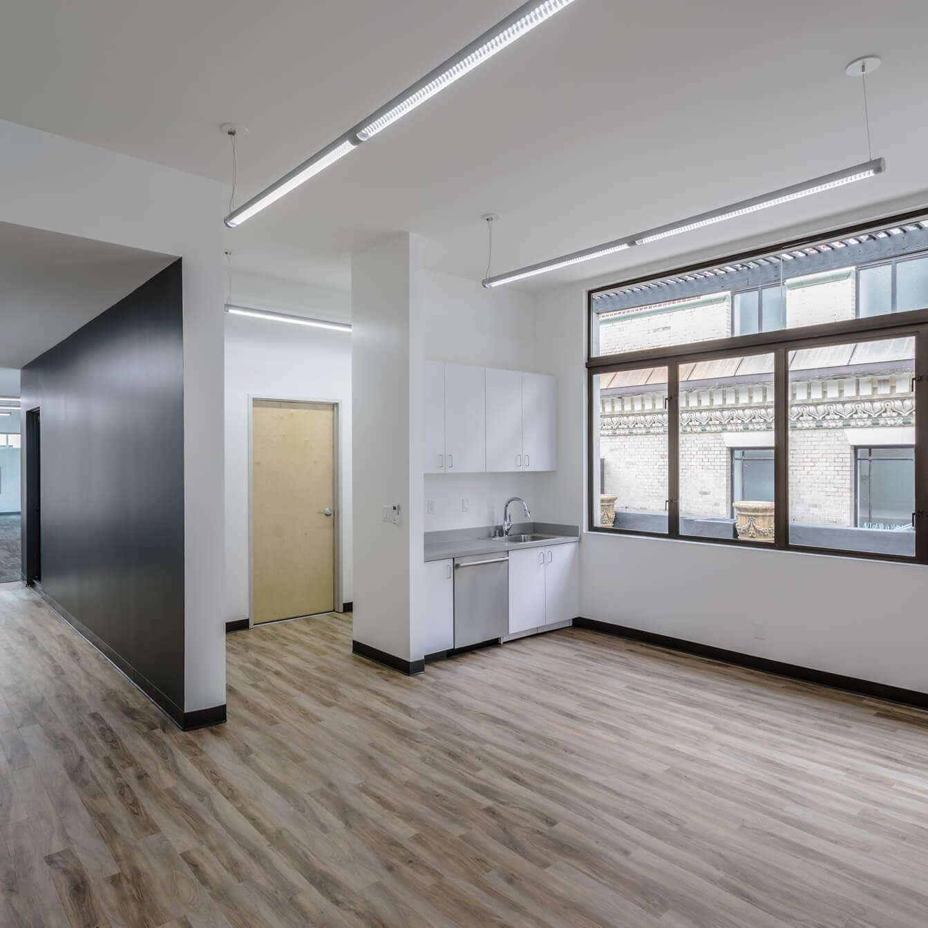 The Athletics san francisco office having a large room with wooden flooring and large glass window