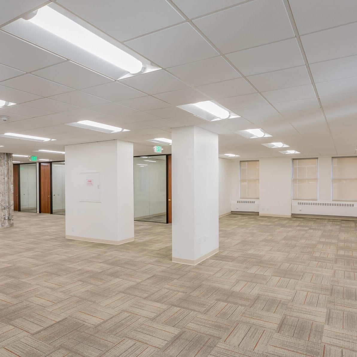 a large room with white concrete pillars and wooden flooring