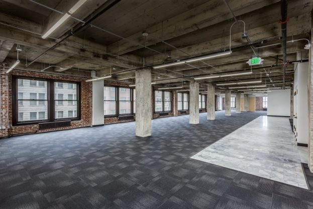 office space with black flooring and pillars