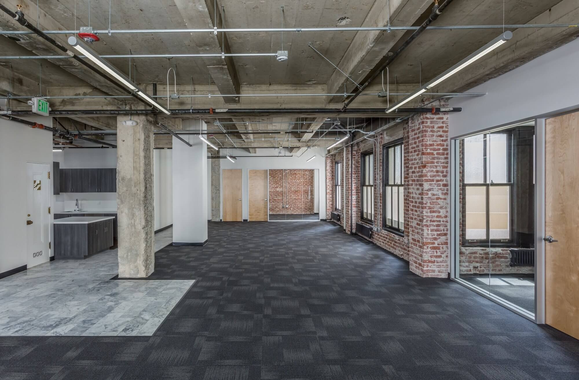office space with black flooring, pillars, white walls and brown doors