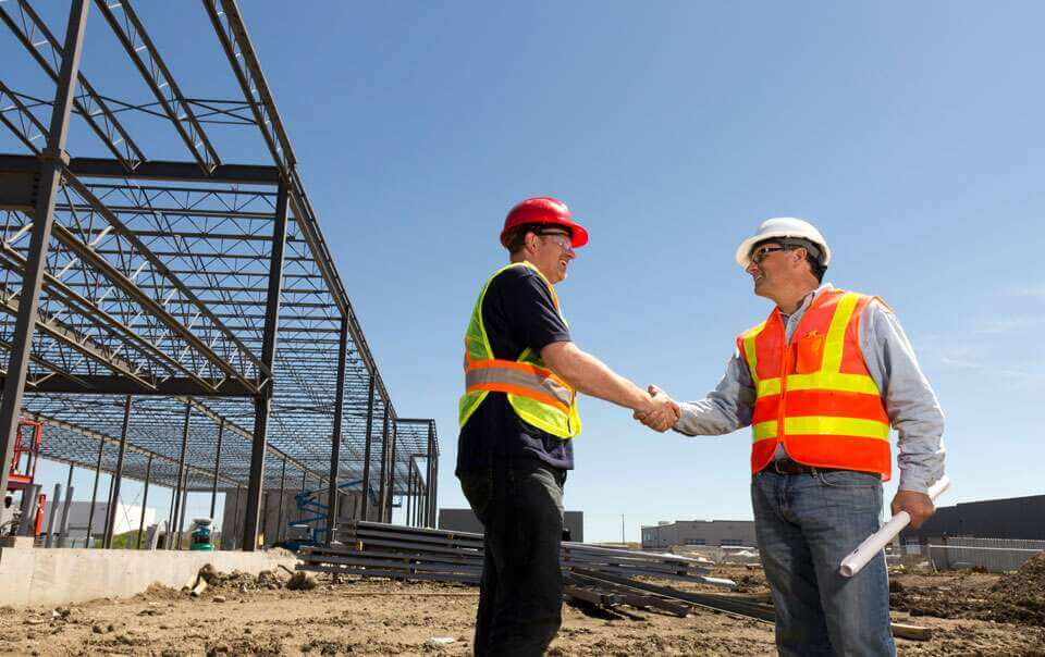 2 general contractors shaking hands at construction site in san francisco