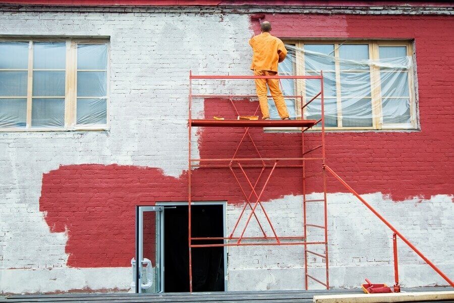 a person in a red brick building painting the wall in red color