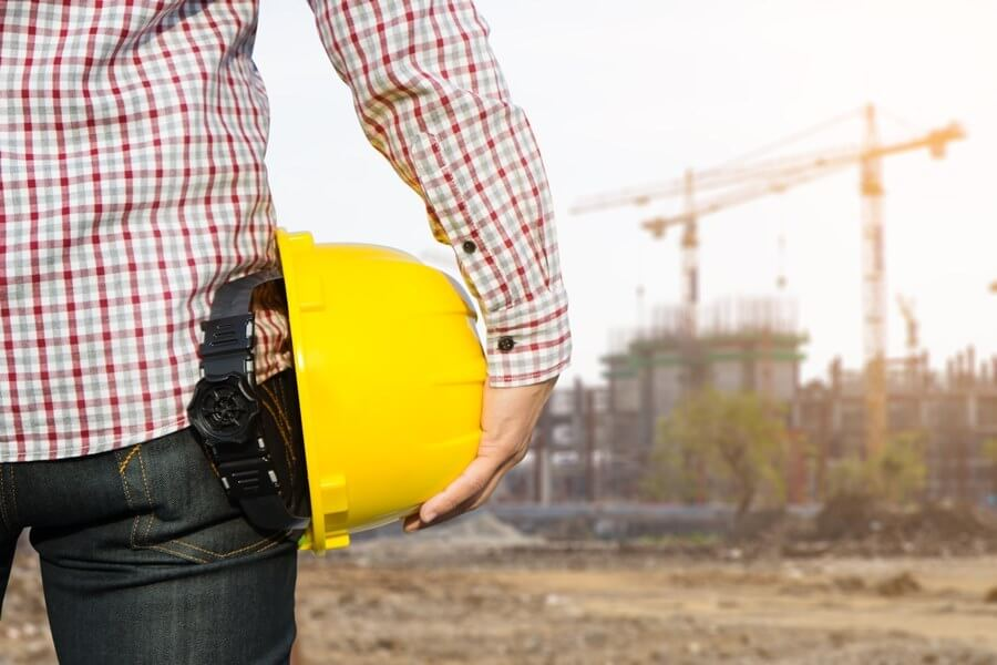 Hand's engineer worker holding yellow safety helmet with buildin