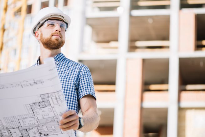 commercial construction manager holding blueprint of construction plan