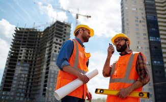 commercial contractor speaking on walkie-talkie with co-worker near by