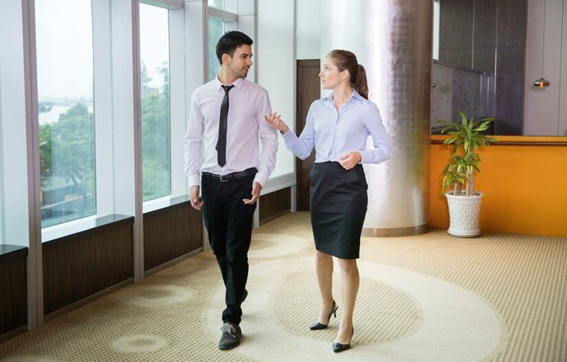 Two young female and male business people discussing something and walking along window in office. Woman is gesturing.