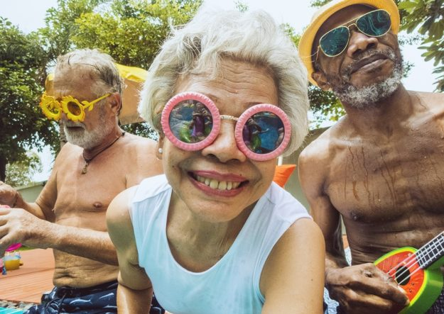 diverse senior adults sitting by the pool enjoying summer together